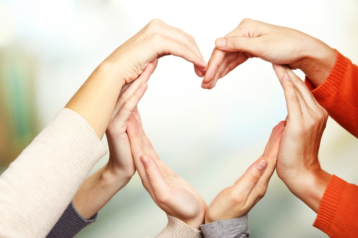 Human hands in heart shape on bright background