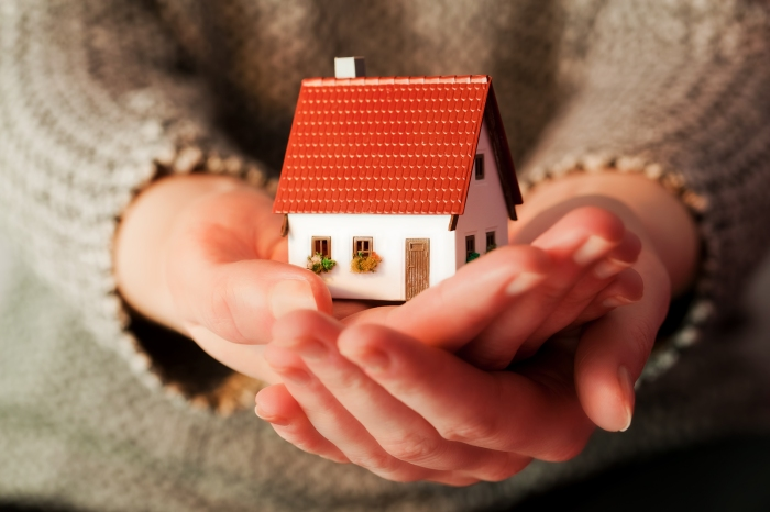 Woman holding a small new house in her hands. Real estate, mortg